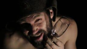有假笑的可怕邪恶的阴险有胡子的人,拿着一个瓶藤和玻璃 有赤裸躯干的奇怪的俄国人 股票录像