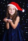 有假雪的愉快的圣诞老人女孩在手上 图库摄影