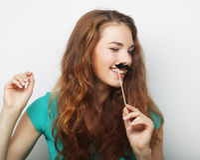 有假髭的年轻愉快的妇女 库存图片
