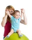 有做与体操球的愉快的婴孩的母亲锻炼 关心的概念对孩子健康 库存照片