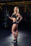 有做与哑铃的被晒黑的身体的坚强的运动的女子爱好健美者锻炼在健身房 体育和健身 免版税库存照片