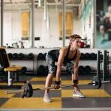 有做与杠铃的运动身体的坚强的妇女锻炼在健身房 免版税图库摄影