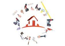 有做与红色房子的工具的很多手一个圈子中部的 库存图片