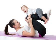 有做体操锻炼的婴孩的母亲 免版税图库摄影