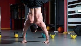 有做在他的手上的赤裸躯干的运动员俯卧撑,当站立颠倒时 影视素材