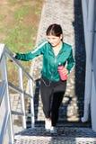 有做在台阶的完善的身体的一名年轻运动的妇女锻炼室外 免版税库存图片