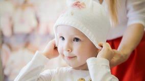有做在孩子的妈妈的小愉快的女孩购物和购买帽子穿戴商店 免版税库存照片