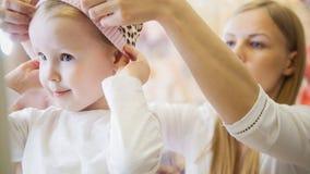 有做在孩子的母亲的小女孩购物和购买帽子穿戴商店 免版税库存图片