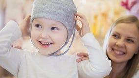 有做在孩子的母亲的小白肤金发的女婴购物和购买帽子穿戴商店 免版税库存照片