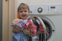 有做在家庭内部的衣裳的愉快的逗人喜爱的小女孩洗衣店 库存照片