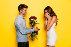 有做婚姻的提议他的女朋友的定婚戒指和玫瑰的人 图库摄影