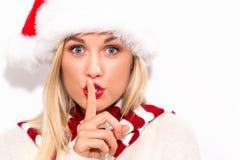 有做安静的姿态的圣诞老人帽子的妇女 免版税库存图片