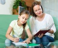 有做家庭作业的女儿的母亲 免版税库存图片