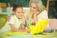 有做家庭作业的小女孩的祖母 库存图片