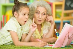 有做家庭作业的小女孩的祖母 免版税库存照片