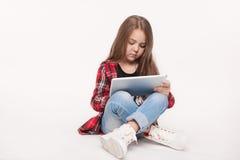 有做家庭作业的片剂个人计算机的小学生女孩 库存图片