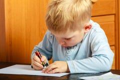 有做家庭作业的笔文字的男孩孩子 胳膊详述她的家庭意图 库存照片