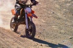 有做尘云的一位被弄脏的摩托车越野赛竟赛者的被聚焦的土路 库存照片