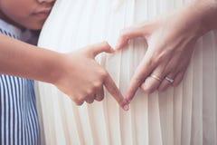 有做手心脏形状的怀孕的母亲的亚裔儿童女孩 免版税库存图片