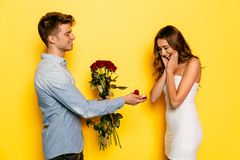 有做提议的定婚戒指和玫瑰的人婚姻对女朋友 库存照片