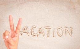 有做文本假期的文本的男性手在沙子 免版税库存照片