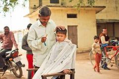 有做新的发型的不快乐的面孔的学龄前孩子由村庄理发师 免版税库存图片