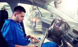 有做汽车诊断的膝上型计算机的技工人 库存照片