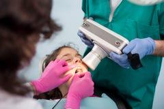 有做牙齿治疗耐心女孩的助理的小儿科牙医使用牙齿X光机在牙齿办公室 图库摄影