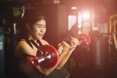 有做的锻炼妇女与杠铃 健身、体型、锻炼和健康生活方式概念 库存照片