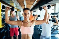 有做的年轻可爱的妇女行使与健身房的朋友 免版税库存照片