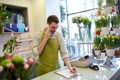 有做笔记的智能手机的人在花店 免版税库存图片