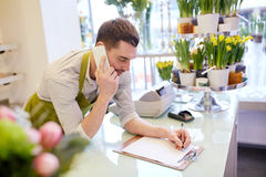 有做笔记的智能手机的人在花店 免版税库存照片