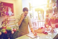 有做笔记的智能手机的人在花店 免版税图库摄影