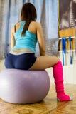 有做被定调子的身体的美丽的健身妇女坐健身球和行使 库存图片