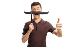有做赞许姿态的假髭的十几岁的男孩 免版税库存图片