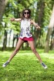 有做跳高的Dreadlocks的活跃和愉快的非裔美国人的十几岁的女孩 免版税库存照片