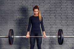 有做deadlift锻炼的重量杠铃的妇女 免版税库存照片