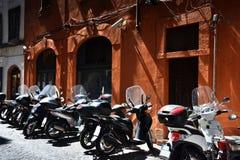 有停放的摩托车的狭窄的街道在罗马 图库摄影