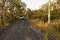 有停放的汽车的澳大利亚土路在日落 免版税库存照片