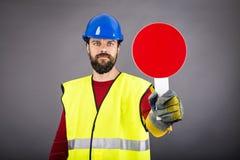 有停止交通的安全帽的年轻建筑工人,举行 库存照片