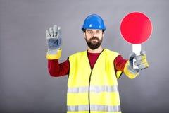 有停止交通的安全帽的年轻建筑工人 免版税库存照片