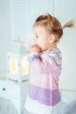 有停留在床上的马尾辫的惊奇白肤金发的小女孩 免版税库存照片