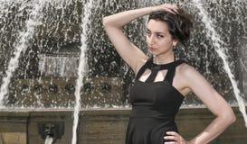 有停滞她的头发的黑礼服的美丽的女孩,古老喷泉在背景中 库存图片