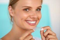 有健康白色牙的妇女使用牙漂白小条的 免版税库存图片