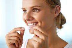 有健康白色牙的妇女使用牙漂白小条的 库存照片