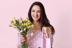 有健康皮肤的,暴牙的迷人的微笑愉快的白种人年轻女人,从丈夫接受礼物在妇女天,拿着礼物袋子 免版税图库摄影