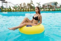 有健康被晒黑的皮肤的美丽的性感的妇女在放松在与橡胶环的游泳池水中的比基尼泳装 免版税库存照片