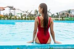 有健康被晒黑的皮肤的美丽的性感的妇女在放松在游泳池水中的比基尼泳装 免版税库存图片