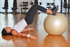 有健身房球的少妇在健身房 免版税库存图片