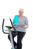 有健身机器和使用的片剂个人计算机女性资深火车 库存照片